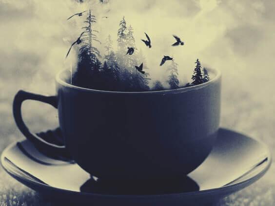 Xícara de chá com floresta e pássaros voando