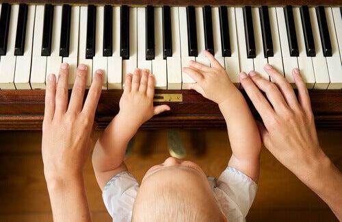 Pai tocando piano com seu bebê