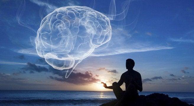 Homem meditando diante de cérebro no céu