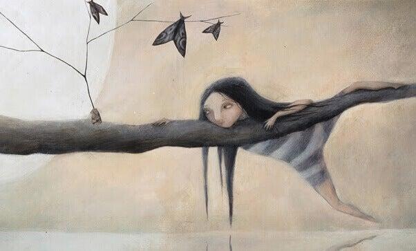 Menina pendurada em galho de árvore