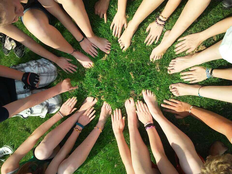 Pessoas com pés e mãos unidos