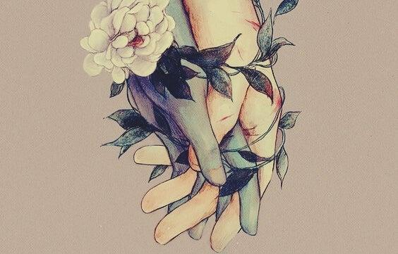 Mãos entrelaçadas com flores e folhas