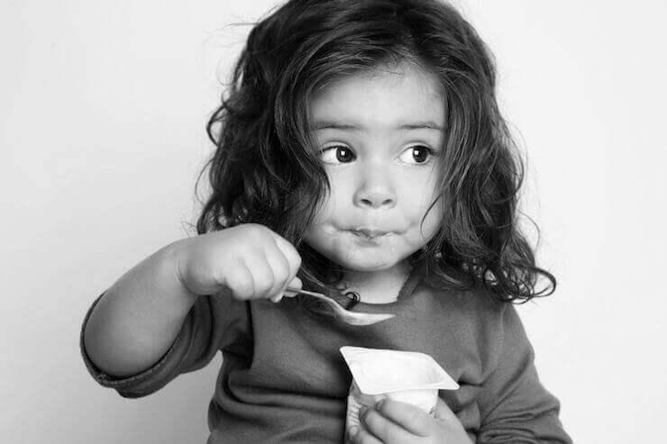Menina tomando um iogurte