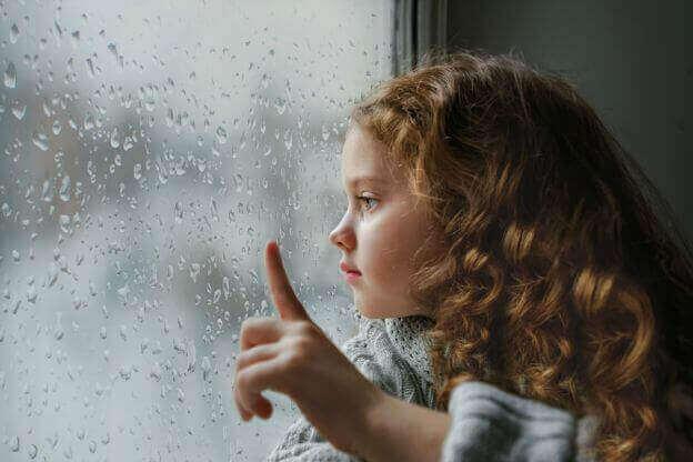Menina olhando pela janela