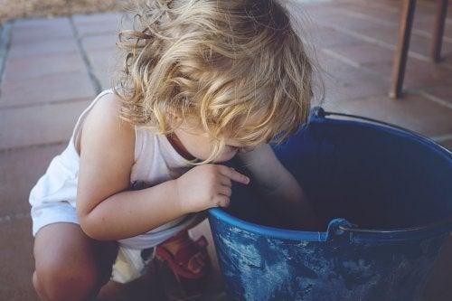 Criança brincando em balde