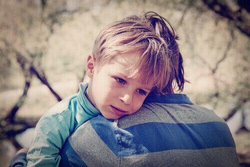 Menino triste abraçado com o irmão