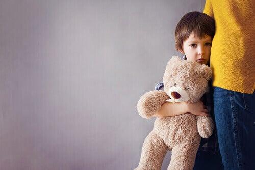 Criança com medo segurando ursinho