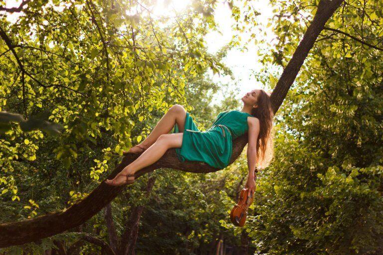 Mulher sentada em galho de árvore