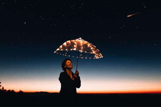 Mulher segurando guarda-chuva iluminado