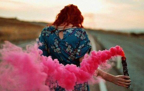 Mulher segurando fumaça cor-de-rosa