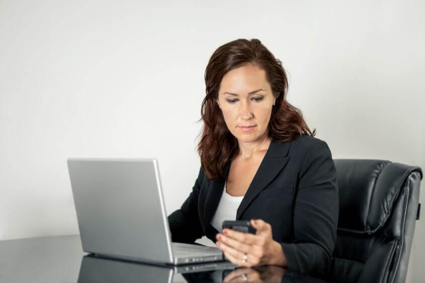 Mulher trabalhando e olhando o celular