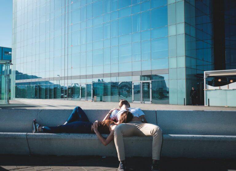 Casal dormindo em banco