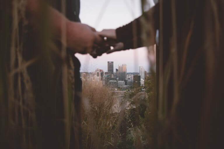 Casal de mãos dadas diante de paisagem
