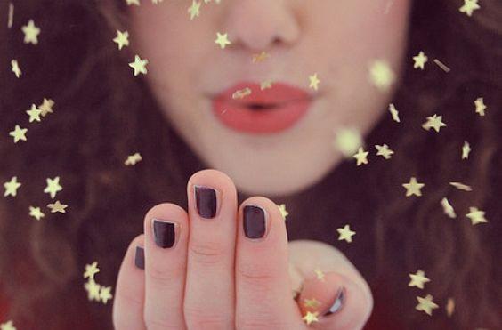 Mulher soprando estrelas douradas