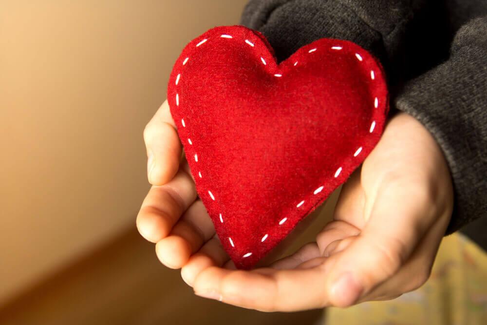 Mãos segurando coração vermelho