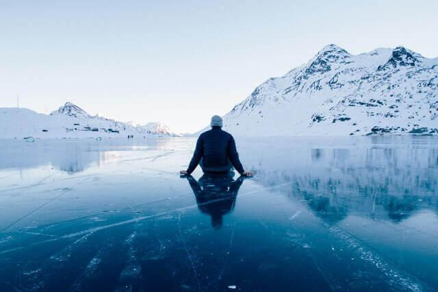 Homem sentado em lago congelado
