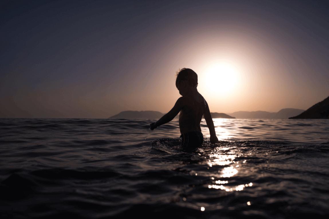 Criança brincando no mar