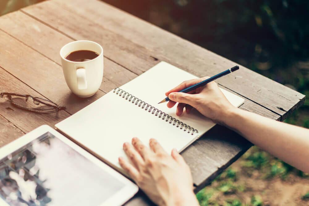 Pessoa estudando com uma xícara de café