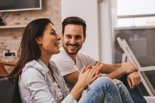Casal conversando e sorrindo em casa