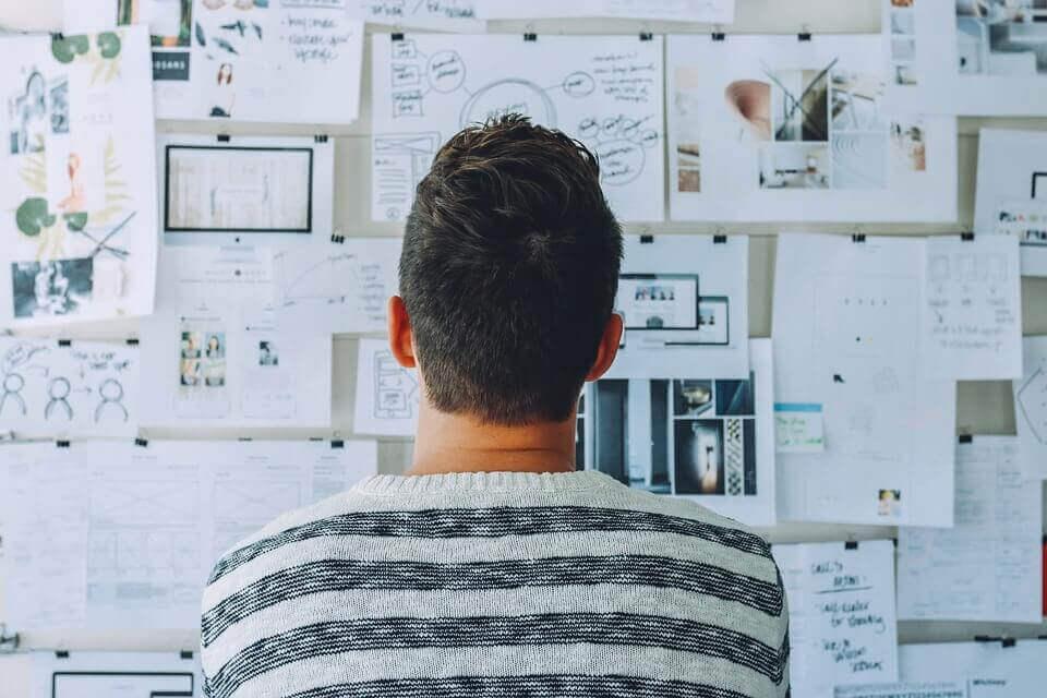 Homem observando mural de ideias