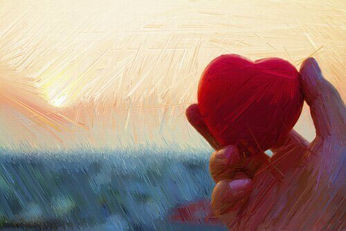 Mão segurando coração vermelho