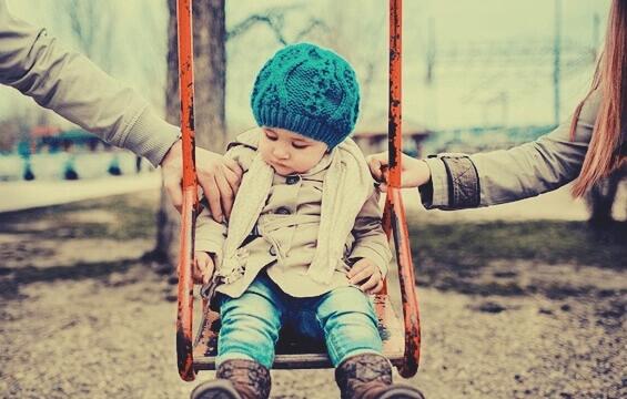 Pais segurando filho em balanço