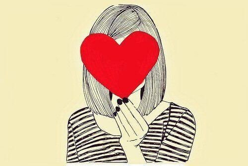 Mulher com um coração tampando o rosto
