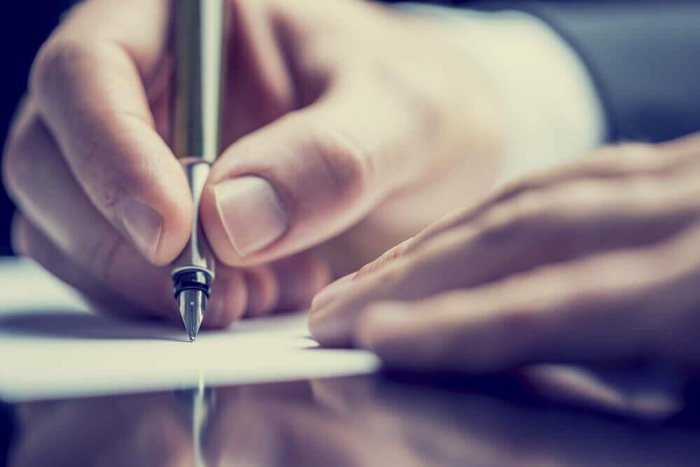 Homem escrevendo com caneta