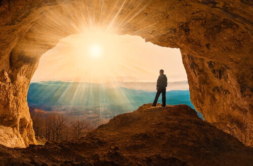 Homem em caverna diante do sol