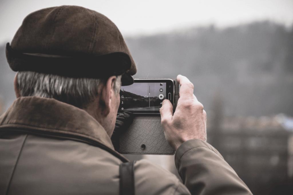 Homem idoso tirando foto com celular
