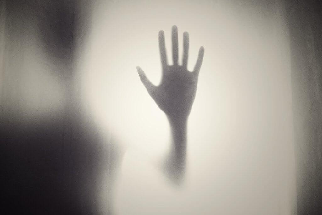 Mão encostada em vidro
