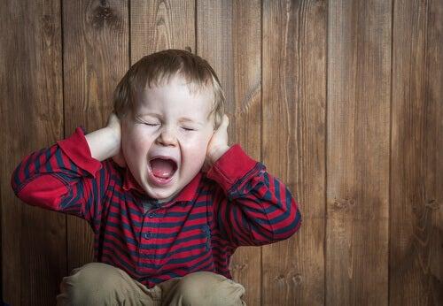 Criança gritando e tampando os ouvidos