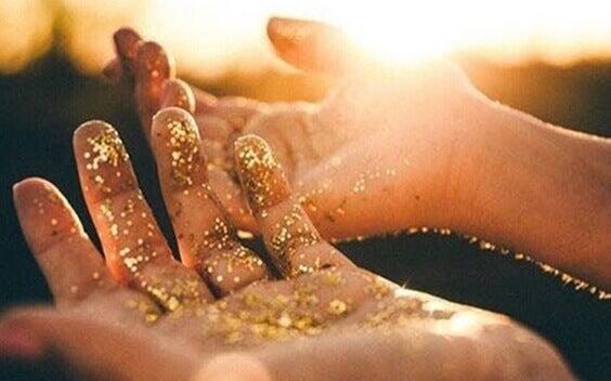 Mão com pó dourado
