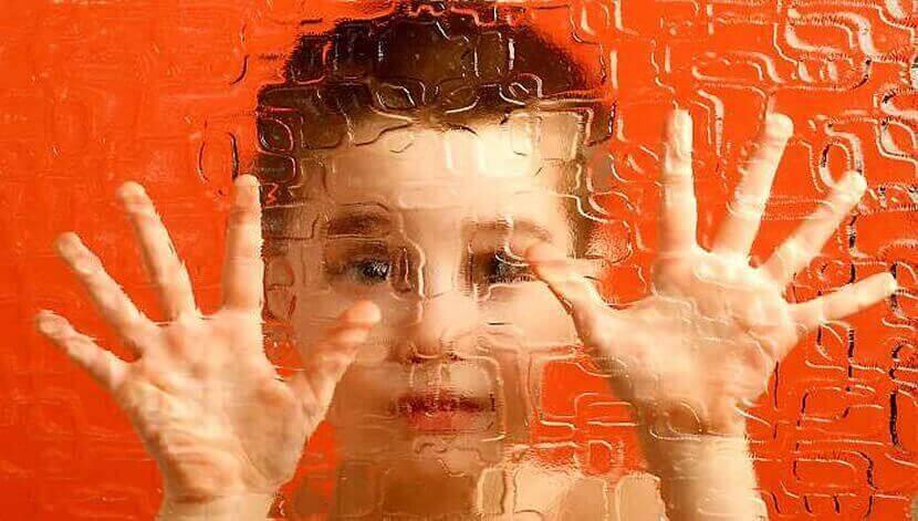 Criança diante de vidro com desenhos