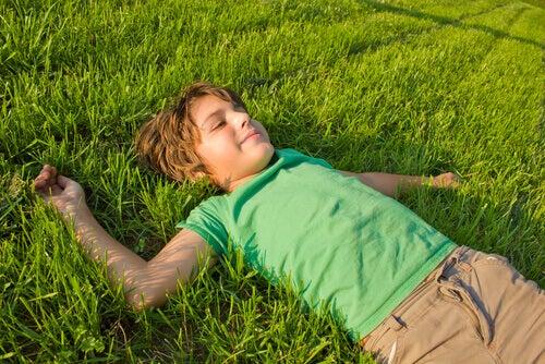 Menino relaxando deitado na grama