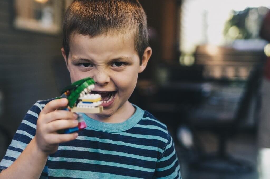 Menino brincando com dentadura