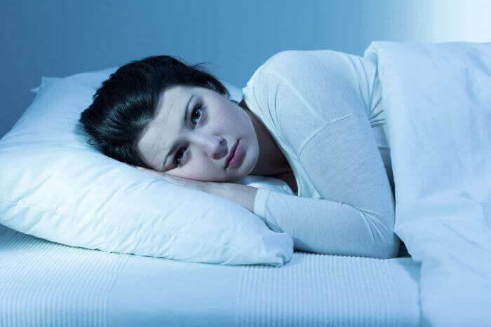 Mulher com insônia, sem conseguir dormir