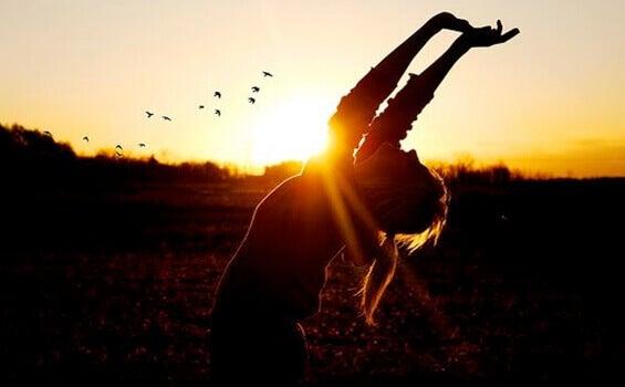 Mulher comemorando diante do pôr do sol