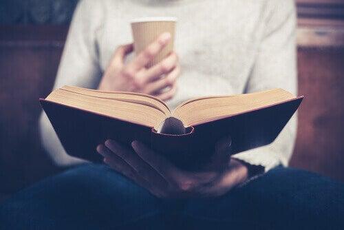 Pessoa tomando café e lendo um livro