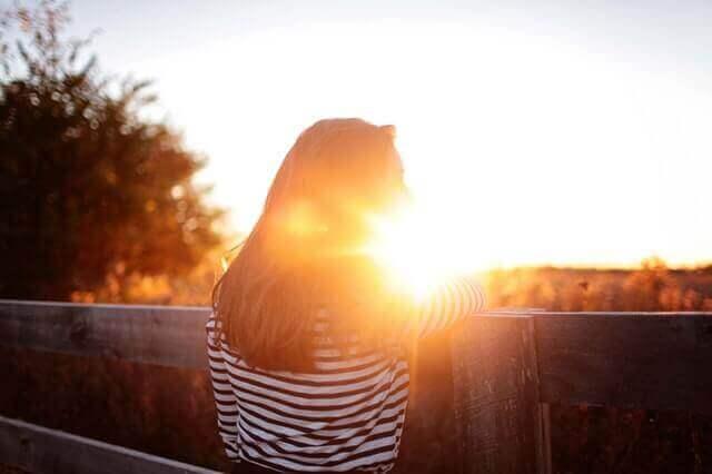 Mulher refletindo diante do pôr do sol