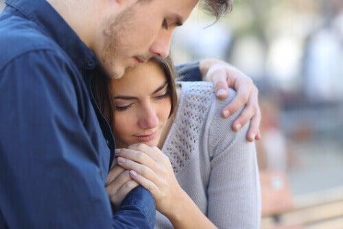 Mulher chorando em ombro de homem