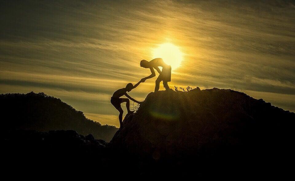 Pessoa ajudando a outra a subir montanha