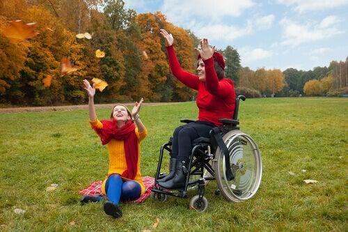 Mulher se divertindo no outono em cadeira de rodas