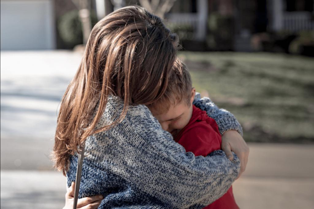 Mãe abraçando filho com deficiência