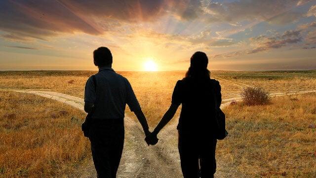 Casal observando o pôr do sol de mãos dadas