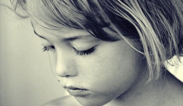 Menina triste com o olhar baixo