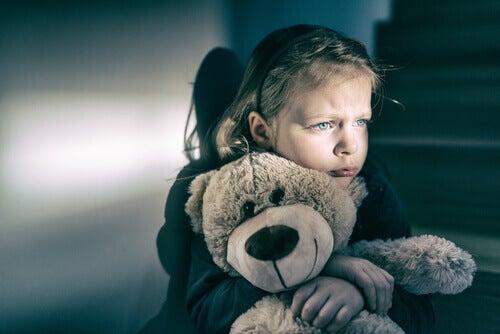 Menina triste abraçando ursinho de pelúcia