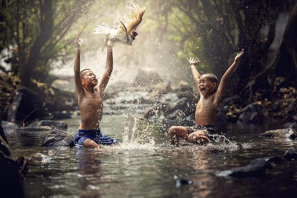 Crianças asiáticas brincando em rio
