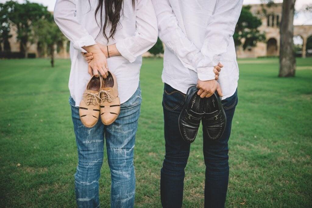 Homem e mulher segurando seus sapatos