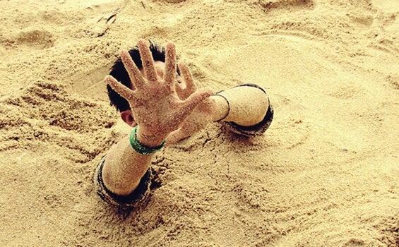 Homem enterrado na areia